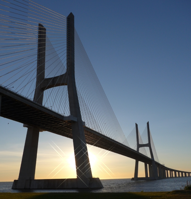 The sun rising behind the Vasco de Gama bridge spanning the River Tagus in Lisbon. Completed in 1998 in time for the Expo 98 World Fair. Europe's longest bridge at 17.2 km